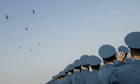 Chinese People's Liberation Army Air Force officers watch helicopters during a celebration.