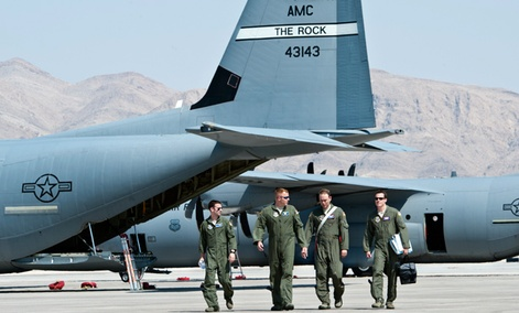 U.S. Air Force Weapons School students and evaluators walk on the flight line at Nellis Air Force Base, Nev.