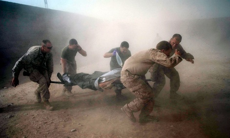 U.S. Marines rush a colleague wounded in an IED strike to a helicopter for evacuation.