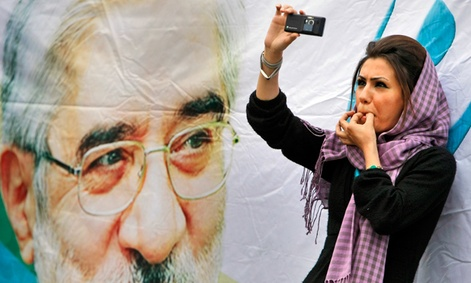An Iranian protester films an election rally in Tehran on her smart phone.