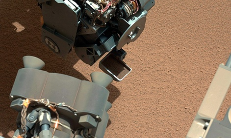The Curiosity Rover uses it's robotic arm to scoop sand.