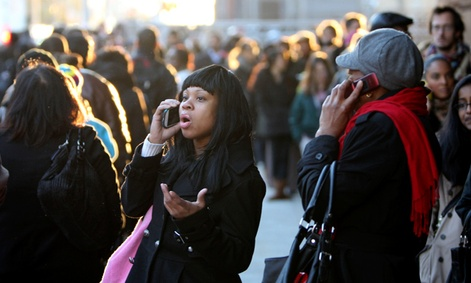 Commuters talk on their phones while waiting in a line to board buses into Manhattan in the wake of Hurricane Sandy.