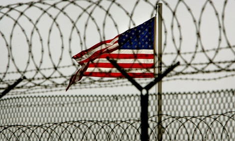 An American flag waves behind the razor-wire fences within the Camp Delta military-run prison at Guantanamo Bay.