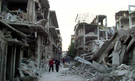 Syrian citizens walk in a destroyed street that was attacked on Wednesday by Syrian forces warplanes.
