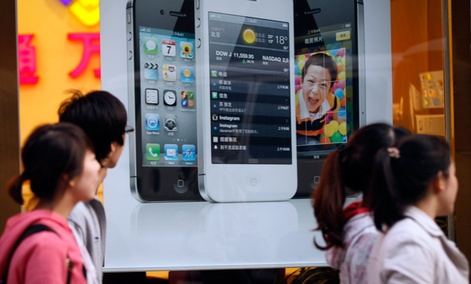 Chinese walk in front of an iPhone poster at a phone shop in Beijing Saturday, April 7, 2012.