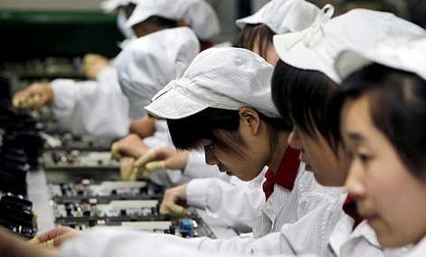 Staff members work on the production line making Apple products at the Foxconn complex in Shenzhen, China