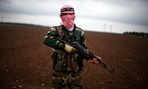 A Free Syrian Army fighter takes position close to a military base, near Azaz, Syria.