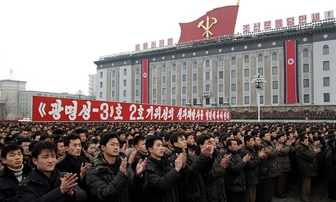 "North Koreans applaud near a slogan which reads ""(we) fervently celebrate the successful launch of the second version of the Kwangmyongsong-3 satellite 2nd version"" during a mass rally in Pyongyang."