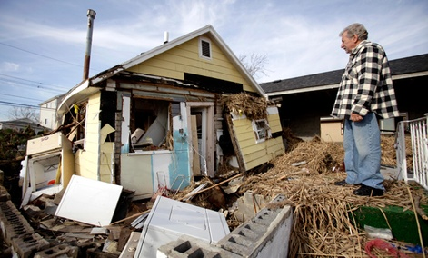Joe Vanvaketis looks at his home from what used to be the stoop of his back door in the Oakwood Beach section of Staten Island, New York.