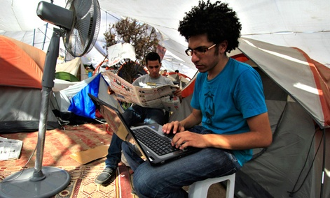 An Egyptian protester uses his laptop next to a cooling fan in Cairo's Tahrir Square in July 2011.