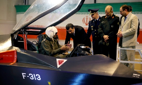 Iranian President Mahmoud Ahmadinejad, center, listens to an unidentified pilot during a ceremony to unveil Iran's newest fighter jet, Qaher-313.