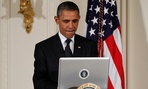 "President Barack Obama uses a laptop computer to send a tweet during a ""Twitter Town Hall."""