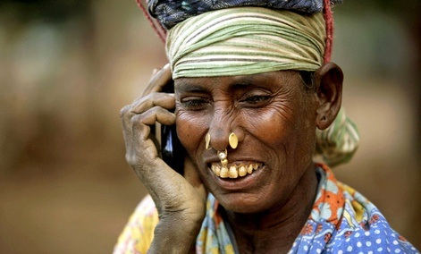 An Indian daily wage laborer talks on a mobile phone, at a construction site in Bhubaneshwar, India.