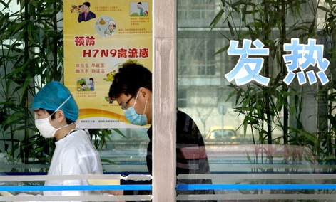 A nurse escorts a man to take a blood test at a specialized fever clinic inside the Ditan Hospital, where a Chinese girl has been admitted for the H7N9 strain of bird flu, in Beijing.