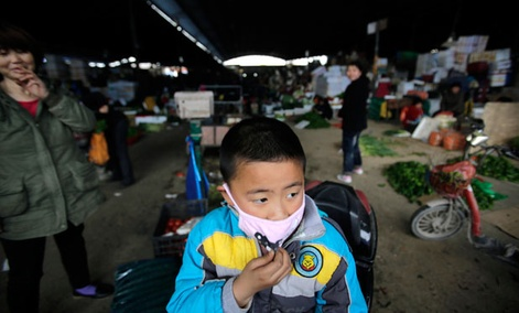 A child wears a mask near the closed poultry section at the Huhuai agricultural market where the H7N9 bird flu was detected by authorities in Shanghai, China.