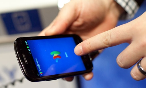 A person tries a smartphone loaded with Google Wallet