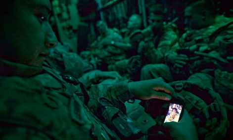 Staff Sgt. Rulberto Qjendismiranda with the U.S. Army's 2nd Battalion 27th Infantry Regiment looks at his mobile phone while aboard a military transport flight.