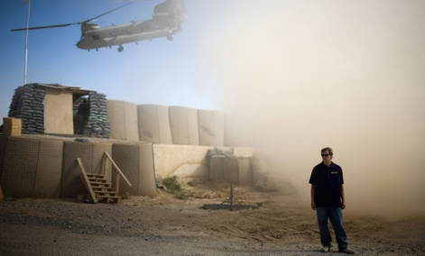 A U.S. contractor stands while a helicopter departs over the gatepost at Combat Outpost Terra Nova in Kandahar, Afghanistan.