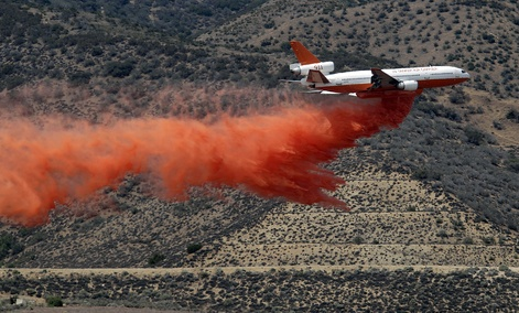 A DC-10 aerial tanker drops a line of fire retardant along the foothills of the Angeles National Forest Sunday.