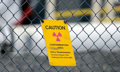 A sign warning of radioactive contamination dangles from a fence at the 'C' Tank Farm at the Hanford Nuclear Reservation.
