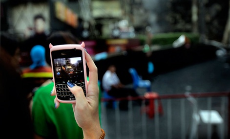 A girl takes a photograph from her mobile phone in downtown Bangkok.