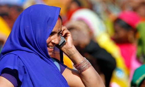 An Indian woman talks on her mobile phone at an election rally in Faizabad, India.