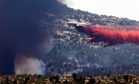 An aerial tanker drops fire retardant on a wildfires threatening homes near Yarnell, Ariz., Monday, July 1, 2013.