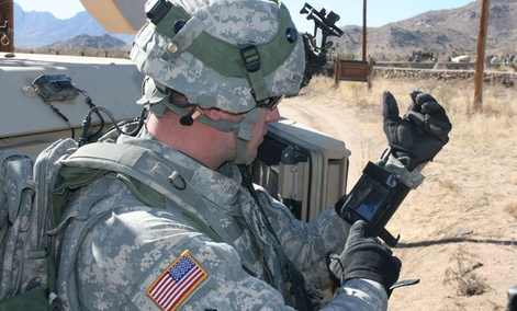A soldier checks an iPhone during a field exercise.