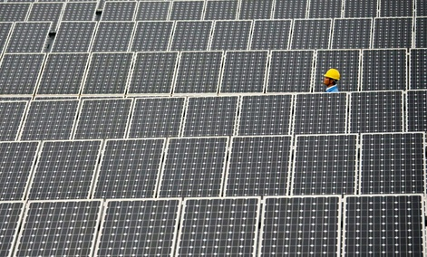 A worker walks past solar panels in a 20 Mega Watt solar farm in southwest China's Yunnan province.