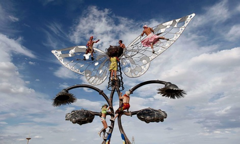 Burning Man participants reach for the skies in a different way, by climbing on an art structure during the festival.