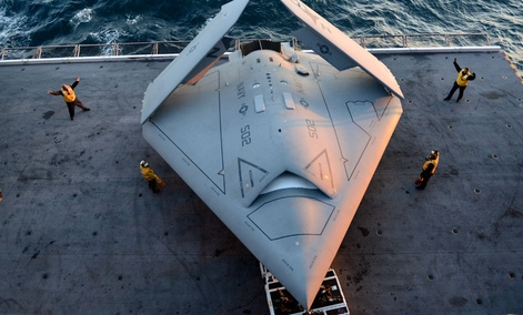 Sailors moving an X-47B Unmanned Combat Air System, which was the first unmanned craft to catapult launch from an aircraft carrier.