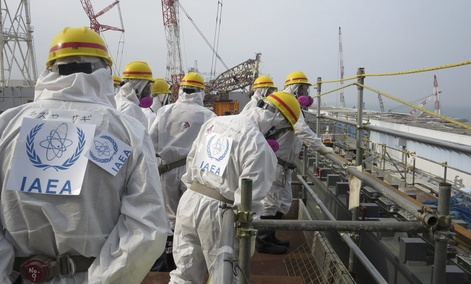 an International Atomic Energy Agency team wearing protective gear inspects the fuel storage pool of the No. 4 reactor building at Fukushima Dai-ichi nuclear power plant.