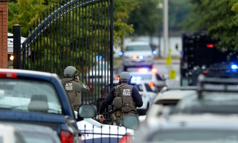 Law enforcement personnel walk through a gate into the Washington Navy Yard.