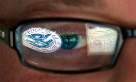 A reflection of the Department of Homeland Security logo is seen reflected in the glasses of a cyber security analyst.