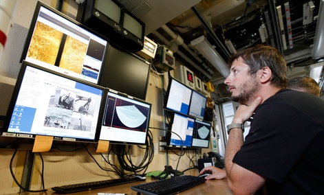 A NOAA employee analyzes data from a sonar system. Roughly half of NOAA employees have been furloughed during the government shutdown