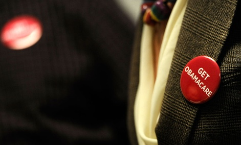 """Associates at Community Health Center wear buttons reading """"Get Obamacare"""" during a session to enroll people on Oct. 1 in New Britain, Conn."""