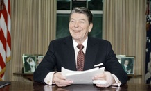 President Ronald Reagan poses for photographers in the Oval Office.