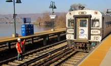 A worker on the track gestures to the engineer of a Metro-North Railroad commuter train pulling into the Spuyten-Duyvil station in the Bronx, N.Y.