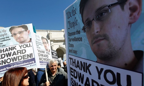 Demonstrators holds up banners with the photo of Edward Snowden during a protest outside in Washington in October.