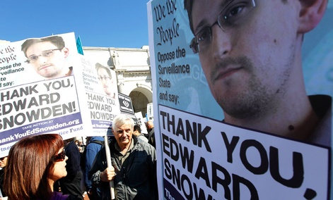 Demonstrators holds up banners with the photo of Edward Snowden during a protest outside of the U.S. Capitol in Washington.