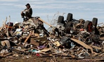 A man sits atop a pile of rubble after a tornado came through Oklahoma in May.