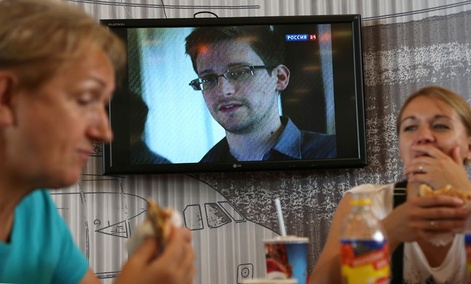 Two Russians eat lunch at Moscow's Sheremetyevo airport while a report about Edward Snowden plays on a nearby TV.