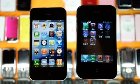 Two different fake iPhones are shown at a mobile phone market