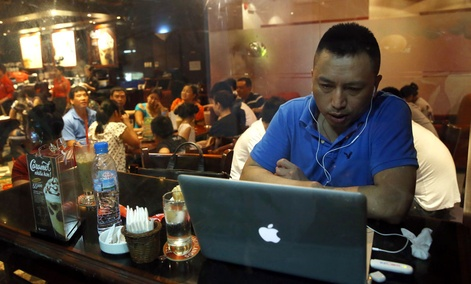 A Vietnamese man uses a laptop to go online by a 3G device inserted into a USB pot at a cafe in Ha Noi, Viet Nam.