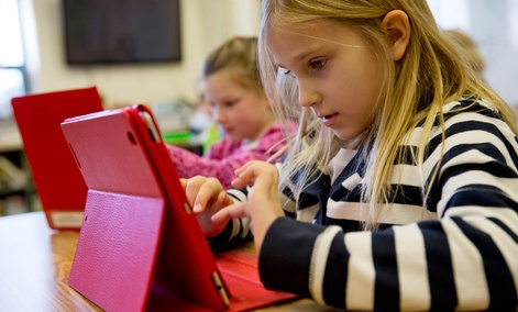 A student works on her iPad during her second grade class.
