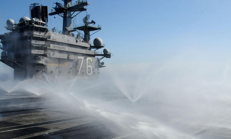 The aircraft carrier USS Ronald Reagan conducts a countermeasure wash down to decontaminate the flight deck while the ship is operating off the coast of Japan in 2011.