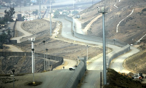 A lone Border Patrol vehicle along with tower mounted video cameras monitor activity along the border fence between Tijuana and San Diego.