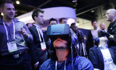 Show attendees play a video game wearing Oculus Rift headsets in January.