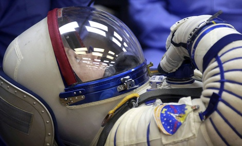 U.S. astronaut Steven Swanson, a crew member of the mission to the International Space Station (ISS) tests a space suit during pre-launch preparations.
