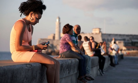 A woman uses her cellphone as she sits on the Malecon in Havana, Cuba